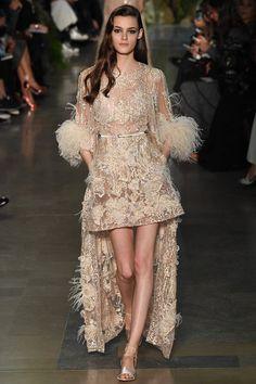 Ливанский дизайнер Эли Сааб в своей новой коллекции Haute Couture весна-лето 2015 щедро декорировал платья невесомыми лебяжьими и страусиными перьями, искусной ручной вышивкой, напоминающей рисунок древесной коры, аппликацией