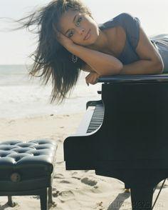 Алиша Киз в длинном облегающем платье играет на фортепиано на берегу моря
