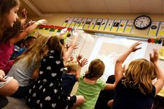 """Evans International Elementary school first grade students raise hands during a reading comprehension lesson Sept. 16. The Sand Creek Zone elementary school began a new curriculum and a school-wide schedule approach is started at the beginning of the 2015-2016 school year. """"It's a double dose of everything and it's already making a difference,"""" said their teacher, Julia Swonger, about the two reading blocks each day."""
