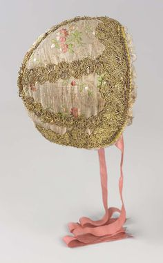 Ground: pinkish orange silk, vestiges of flat gold (gilded silver), powdered with sprays of small pink flowers with green leaves. Trimmed with gold bobbin lace, narrow cream silk bobbin lace around face. Lined with cream colored silk ikat pattern. Deep pink silk ribbon ties. Worn, stained.
