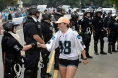 A fan bumps fists with police officers outside Bank of America Stadium in Charlotte, NC on Sunday, September 25, 2016. The Carolina Panthers hosted the Minnesota Vikings in NFL action.