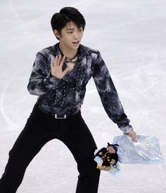 Japans Yuzuru Hanyu waves to fans as he picks up a stuffed animal tossed to him following his skate in the mens short program in the Skate America figure skating event Friday, Oct. 19, 2012, in Kent, Wash.