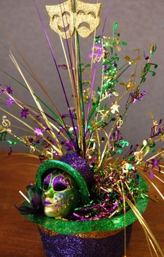 DIY Mardi Gras Centerpiece made from an upside down purple, green, and gold hat filled with foil tensil, onion grass, leaf picks, and ornaments.