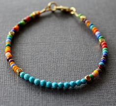 Fun, festive and full of color, this bracelet by Tam Davis adds new life to your casual jewelry collection. The multi colored seed beads and gold plated cube beads are arranged randomly along the sides of a front section of sleeping beauty turquoise to create a eye-catching, graphic