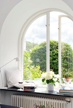 arched window opening to a beautiful view with window ledge holding a glass of wine, a stack of books, pillows, a reading lamp and a potted plant