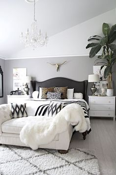 neutral bedroom with crystal chandelier, button tufted chaise, black and white accents and leather studded wingback bed