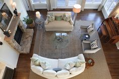 Traditional Family Room Design with Circular Glass Coffee Table and White Curved Sofa also Stone Fireplace
