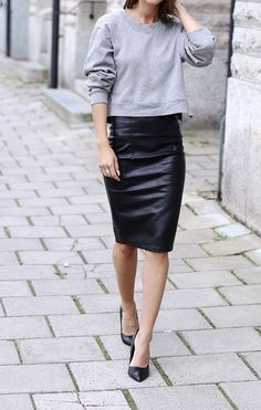 Acheter la tenue sur Lookastic:  https://lookastic.fr/mode-femme/tenues/pull-a-col-rond-gris-jupe-crayon-en-cuir-escarpins-en-cuir/11307  — Pull à col rond gris  — Jupe crayon en cuir noire  — Escarpins en cuir noirs