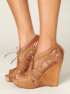 Gorgeous lace-up wedge with elaborate cut-out leather upper, peep toe opening, and zipper closure in the back.