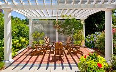 The lattice screen is a beautiful addition to a pergola surrounded by lush vegetation