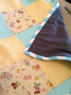 Blue, yellow and character cot quilt with dark grey backing and wadding in the middle. Fits standard cot. https://www.facebook.com/pages/Avie-Designs/230829420318168
