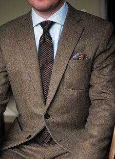 Brown herringbone tweed suit, white shirt with light blue checks, brown tie with white pin dots