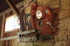 Mounted above the stone fireplace, a rusted front end of a truck with headlights works perfectly with the rustic design of the space.