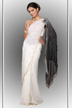 Pleasing Party wear saree in Lemaire Georgette, in the hottest combination ever, White and Black, The always in,beautiful contrast pallu joined with embroidered flower, complements with the saree in perfect style!