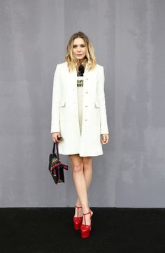 Elizabeth Olsen wears a Gucci mini dress, coat, bag, and platform heels