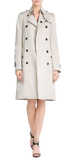 In a timeless shade of pale beige, this cotton coat is a classic iteration of Burberry London's signature trench. Complete with the iconic check lining and double-breasted front, it will never date #Stylebop