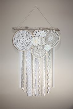 The Large Dream Catcher Wall Hanging has shades of cream and white vintage doilies and beautiful flowers. The hanging consists of different and unique yarn and lace. It also has a one of a kind piece of driftwood at the top that gives it a bohemian look. READY TO SHIP!
