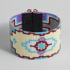 Hand beaded this Native American Desert Flower bracelet on a loom in Albuquerque, New Mexico. The design is made of high quality glass Japanese Delica seed beads in lavender, dove gray, cranberry red, pale yellow, and sky blue with a hint of galvanized silver. The clasp is hand tooled and is as attractive as it is secure. This bracelet measures 7 inches long by 1 1/2 inch wide.