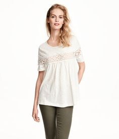 Wide top in cotton slub jersey with a seam at the front with a lace section, short sleeves, and an opening at the back of the neck.