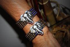 Bracelet Homme en Kente et passant Éléphant   VENDU à l'unité   *** Collection HOMME 2016 ***  -Tissu africain Kente noir, blanc, jaune et bleu -Passant tête d'éléphant en métal argenté -Fermoir aimanté en métal argenté   Les apprêts en métaux sont en aciers inoxydables.  2 Modèles disponibles, A: (bracelet du haut sur photo) Longueur 20 cm Largeur 2 cm Épaisseur 3 mm  B: (bracelet du bas sur photo) Longueur 19,50 cm Largeur 2 cm Épaisseur 3 mm  !!! Lors de votre commande,