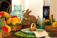 mesa posta temática para páscoa decorada com coelho, cesta de flores amarela e vermelha e suculentas. Mix and match de pratos verdes com guardanapo estampado de coelho e cestinha com ovo de galinha.