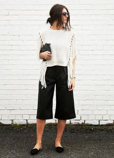 Ellie Mack of Strut in Her Style in a knit fringe top and black culottes
