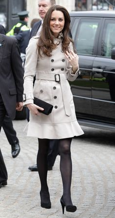 Kate Middleton in Belfast, Northern Ireland, wearing a Burberry trench coat, black tights, and black suede court heels.