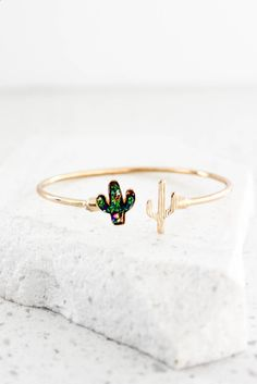 This open ended bracelet features a cactus on both ends. The bulk of this bracelet is done in a gold high polish finish, as well as one of the cactus. The other cactus is decorated in a mix of blue,
