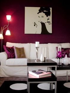 red-violet tones with sterling silver accessories. The white sofa pops against the rich magenta walls and accent pillows. Periwinkle carpet  more tones down the bold color of the room, while still maintaining that lovely pink-purple hue.