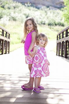 Sibliing photo sweet pose for a photo of two young sisters.  Pink dress and matching shorts make the colors work well together in this picture.