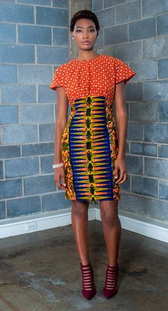 Contrast front pleat skirt in blue and yellow snowflake Dutch Wax Print fabric. This flared knee length skirt, features side pockets and a contrasting front pleat that is cut in a orange and yellow Af