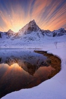 Norwegian mountain bathed in beautiful light and tranquil reflection.