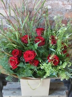 A classic bouquet with red Naomi Roses and lots of crazy seasonal foliage.