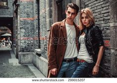 Young and trendy man and woman posing of the street with brick walls. Fashion style - stock photo