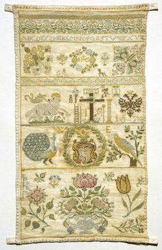 Germany-1674 Band sampler, linen embroidered with polychrome silks with an alphabet, flowers and other motifs including the Lamb of God, Instruments of the Passion, coat of arms, peacock and a large flower vase.  Embroidered with polychrome silks in cross, back, and satin stitch. Edges are finished with buttonhole stitch Fitzwilliam Museum Collections Explorer - Object T.93-1938 (Id:110824)