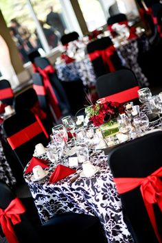 "Classic: Red, Black, and White. This trio will forever be among wedding favs. We love damask patterns. It adds texture and  draws the eye to your reception tables. Coupled with classic red hybrid tea roses or  ""black magic"" roses this color palette is a show-stopper."