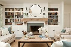 A round black mirror is mounted to shiplap trim between two Boston Functional Library Wall Lights lighting a chunky reclaimed wood mantle fixed above a fireplace accented with a slate surround.
