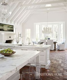 The kitchen, living, and dining areas are open to one another—unified by painted ceiling beams and trusses and terra-cotta floor tiles imported from France. - Photo: Werner Straube / Design: Laura O'Brien