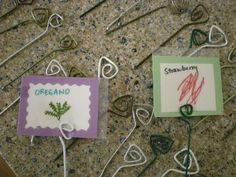 I adore these paper clips made from hanger wire with laminated pictures as garden labels! They look like they are little vines growing up out of the garden along with your plants!