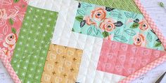Play with Colors and Fabric Styles in This Easy Quilt! This sweet little quilt will be a beautiful addition to a display of small quilts on your wall. It also makes a pretty topper or candle mat for a small table. The light zigzag down the middle pops the other colors and adds interest to …