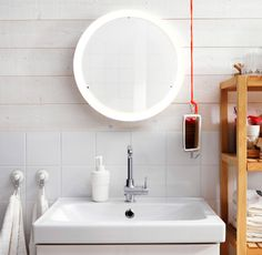Round IKEA mirror with integrated LED lighting on the wall above the sink.