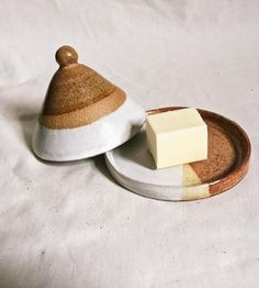 Formed by hand into a small cone shape, this ceramic butter dish features neutral hues and an earthy texture. The golden brown and creamy white glazes create contrast against the raw, matte clay, and the butter dish has seen multiple firings for durability. Just add your favorite spread underneath the cover to set the table for mealtime.