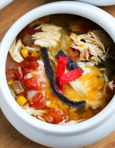 Slow cooker chicken tortilla soup.Chicken breasts with vegetables cooked in slow cooker and served with shredded cheese and tortilla chips