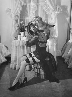 A model combs her hair as she shows off the latest WWII-era fashion in 1943: black cotton stockings with an extra pair of garters to help prevent bagging at the knees — a design created by hose manufacturers in response to the challenge of wartime rayon restrictions.
