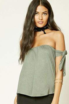 A jersey knit off-the-shoulder top featuring an elasticized neckline, self-tying sleeves, and a cropped silhouette.