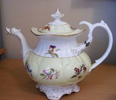 """(C1835) . COALPORT DUCK HEAD SPOUT TEAPOT. 9""""HIGH, X 11""""HANDLE TO SPOUT ALL APROX. WITH HAND PAINTED FLOWERS. OLD STITCHED REPAIR TO HANDLE.10 hole circular strainer."""