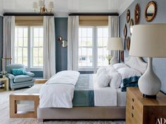 In the guest room of a Bridgehampton, New York, home decorated by the Steven Gambrel, overscale 1960s table lamps flank a Gambrel-designed bed dressed with Pottery Barn sheets. The vintage rattan mirrors came from a Paris flea market.