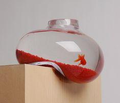 aquarium de forme bizarre avec un gravier rouge et un poisson d'or