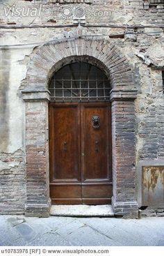 Wooden door with brick archway, Italy.