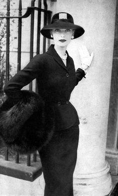 Model in slim black wool suit by Omar Kiam for Ben Reig worn with large fox fur muff, Vogue, October 1, 1951